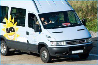 white minibus with yellow sunburst vehicle graphic