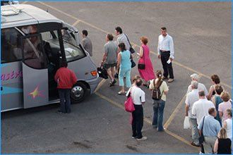 passengers disembarking from coach to make their way to an aircraft