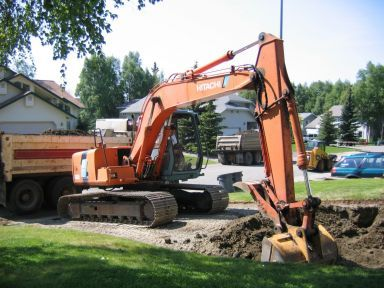 Tractor tearing up driveway by a driveway paving contractor in Anchorage, AK