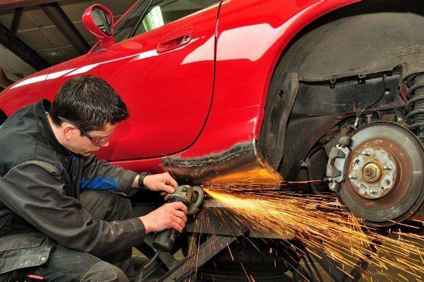 un carrozziere che usa il flessibile sulla carrozzeria di una macchina rossa