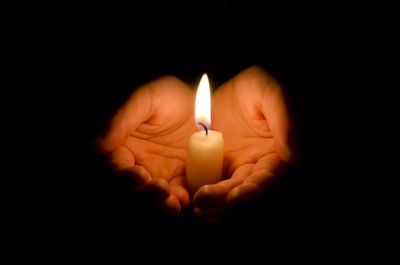 candela accesa tra due mani