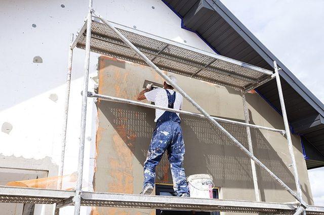 Operaio sta applicando cemento su una parete