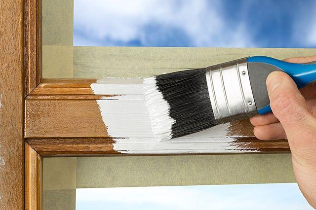 Mano sta imbiancando di bianco una porta di legno