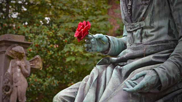 statua funeraria con fiore rosso in mano