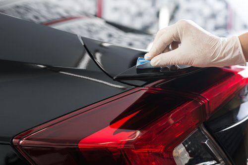 un tecnico che controlla la vernice di una vettura
