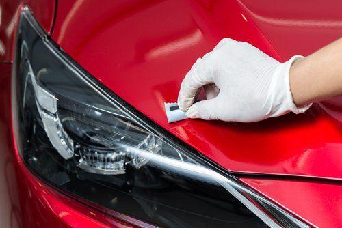 una mano mentre utilizza un abrasivo sulla carrozzeria di un auto