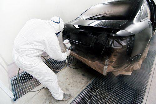 Un addetto mentre utilizza una bombola spray nera per verniciare un'auto
