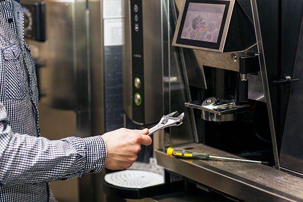 Uomo che ripara una macchina per il caffè