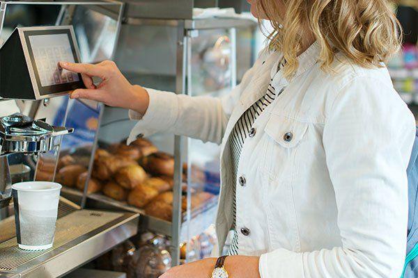 una donna sta utilizzando il distributore automatico del caffè