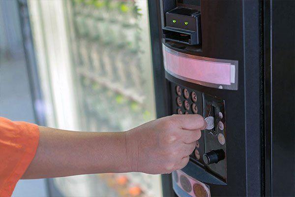 Mano di donna che mette una moneta in distributore automatico di bevande