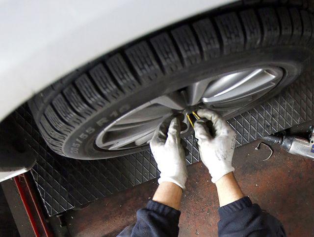 un gommista che sta stringendo bulloni ad una ruota di una macchina