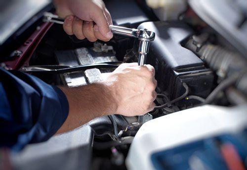 un meccanico con una chiave che svita un bullone di un motore