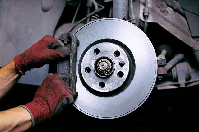 Mechanic changing the brakes on a car in Superior
