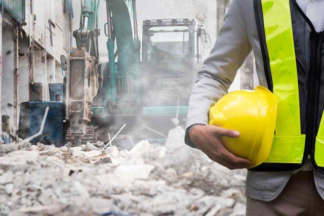 un operaio e una scavatrice che demolisce una casa