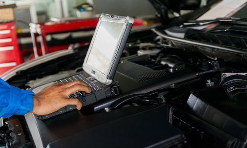una mano che usa un computer portatile appoggiato sul motore di una macchina