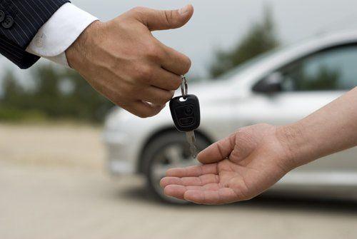 mano passa le chiavi di un'auto a un'altra mano