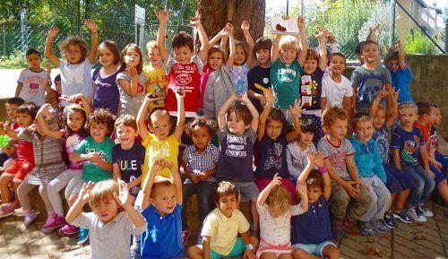dei bambini con le braccia alzate in posa per una foto