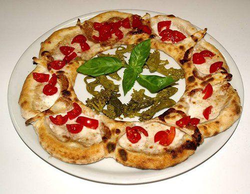 Una pizza cn pomodorini, mozzarella e basilico a forma di fiore