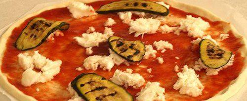 Preparazione della pizza con zucchine alla griglia e mozzarella