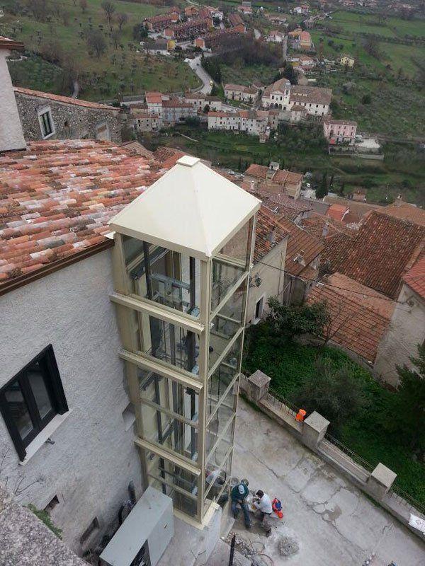 visuale aerea di una struttura cabinata che ospita un ascensore esterna vicino a un'abitazione