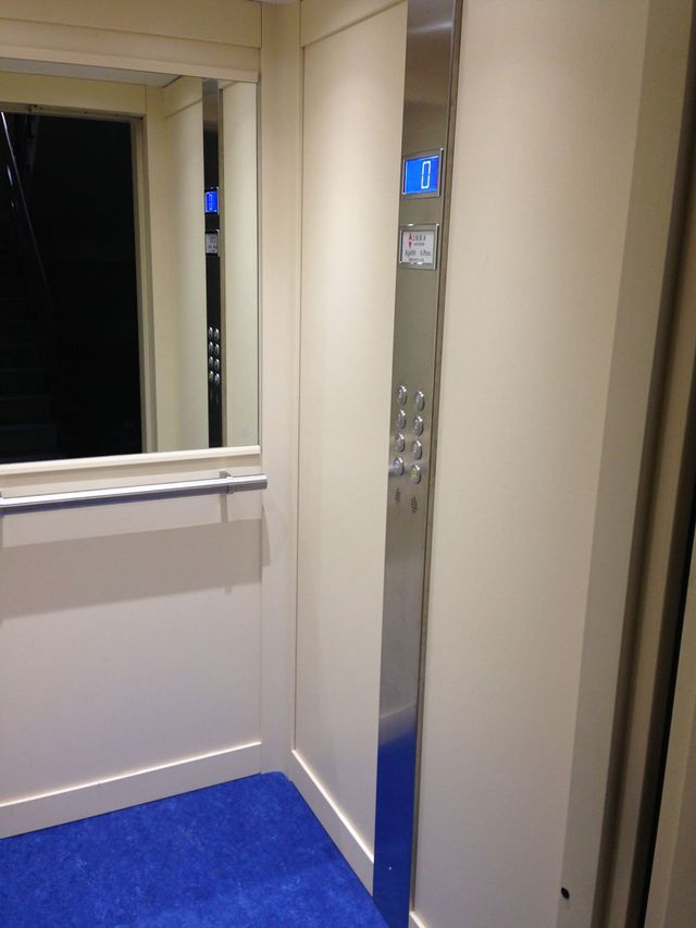 interno di un ascensore con sulla destra vista della pulsantiera e dello schermo lcd azzurro