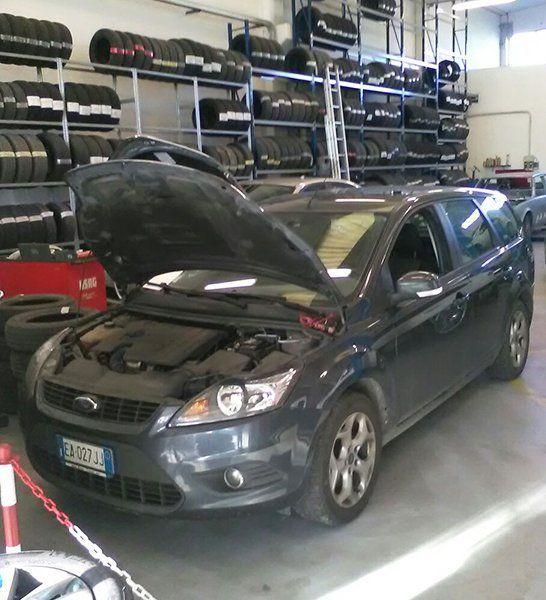 una macchina Ford station wagon di color grigio scuro con il cofano aperto