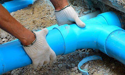 due mani con dei guanti di lana beige che tengono in mano un grosso tubo azzurro