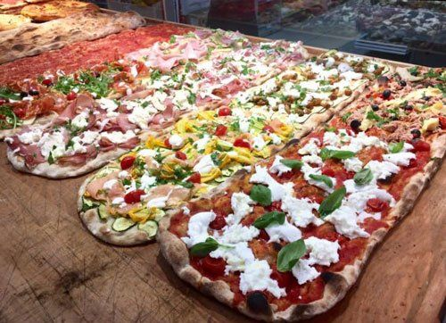 Pizze di diversi gusti sopra ad un piano di lavoro