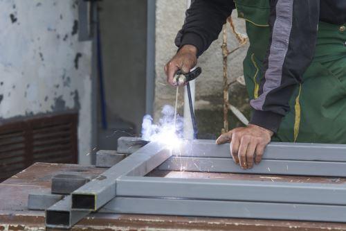 un carpentiere salda dei tubi metallici