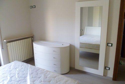 Camera da letto con mobili in legno bianchi e un grande specchio