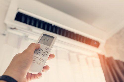 mano che spinge un telecomando per accendere un impianto di aria condizionata