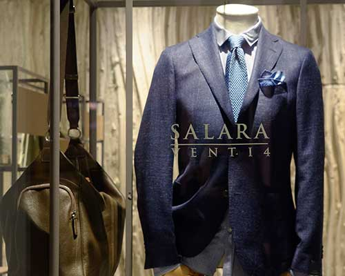 una giacca blu con una cravatta azzurra esposta da Salara Venti 4