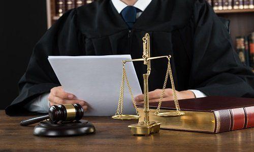 un avvocato seduto con una tunica nera e dei documenti in mano