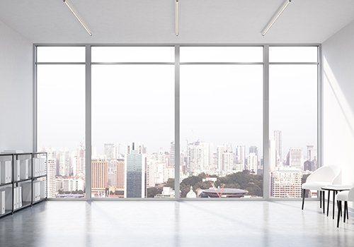 Stanza bianca con sedie bianche e vetrate panoramiche pieghevoli e scorrevoli