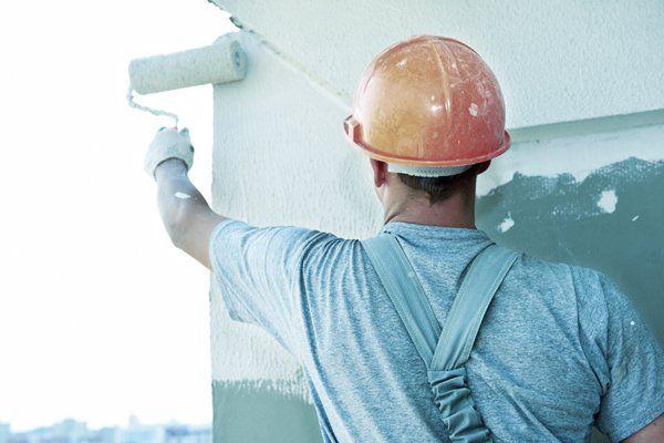 Uomo tinteggia le pareti di una casa