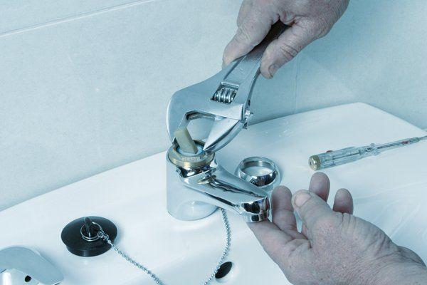 Idraulico ripara un rubinetto