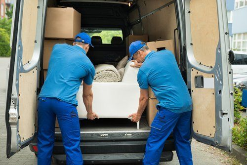 due facchini prelevano delle scatole da un camion traslochi