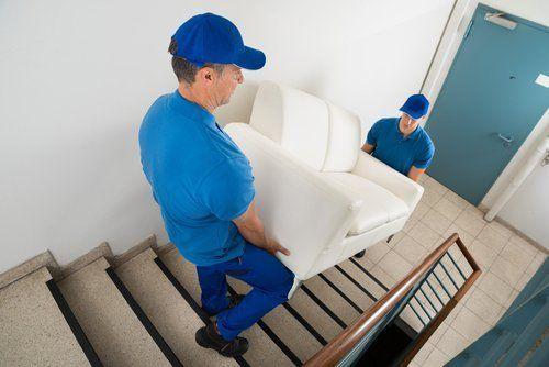 due facchini trasportano un divano giu per le scale