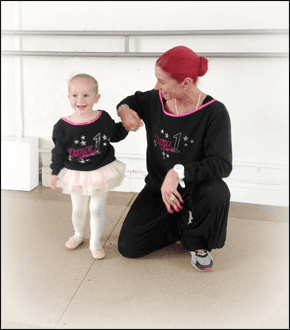woman crouching next to a young girl wearing a ballet outfit with a white wall behind