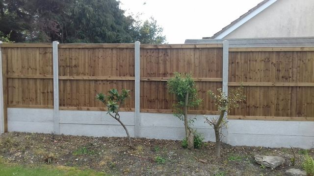A lawn edged with a long timber fence
