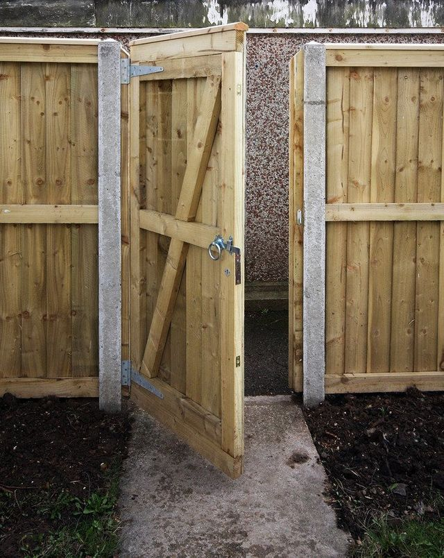 An open timber gate in a garden fence