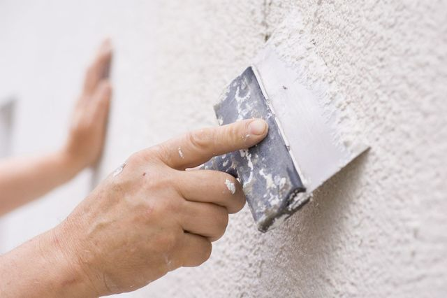 Hands plastering a wall
