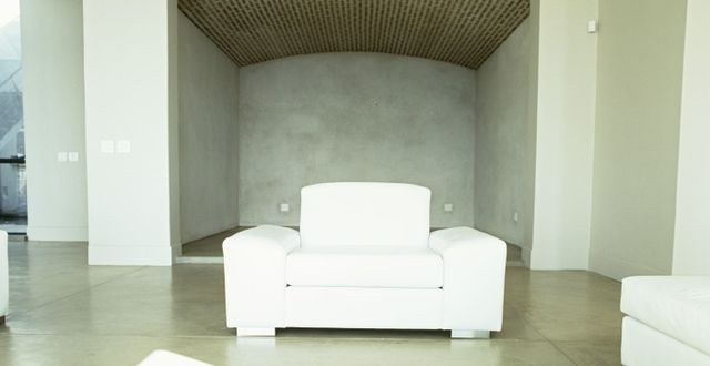 Big white chair in front of a concrete wall