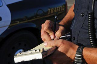 Police officer writing a traffic violation ticket