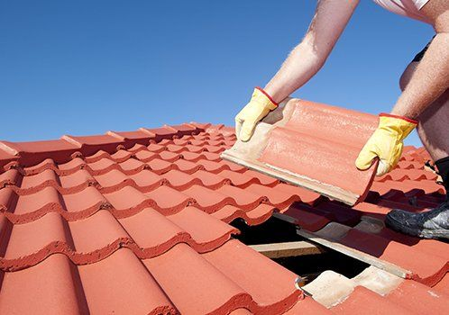 Worker replacing red roof tiles