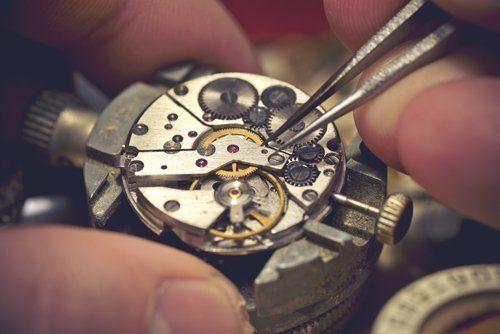 orologiaio mentre sistema un orologio