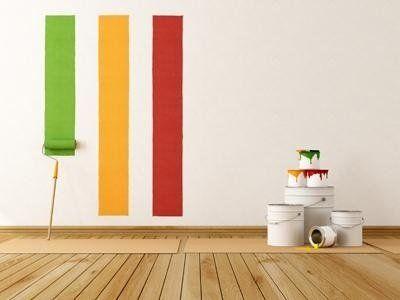 dei secchi di vernice e una parete bianca con tre linee verdi arancioni e rosse