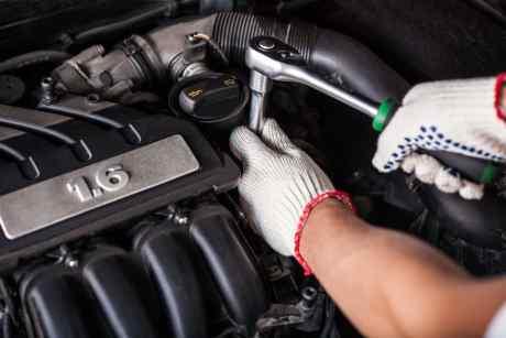 due mani che con un attrezzo svitano un bullone di un motore