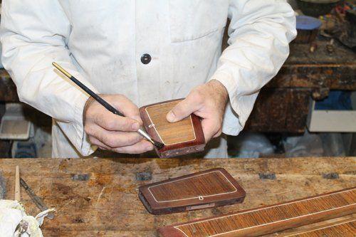 restauratore durante un lavoro di verniciatura su un pezzo di legno