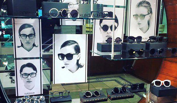 degli occhiali in esposizione e delle foto in bianco e nero di uomini e donne che gli indossano